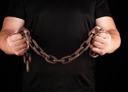 adult man in black clothes stands upright with strained muscles and holds a rusty metal chain,  concept of strength and endurance