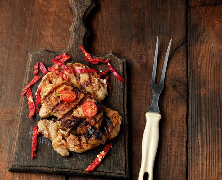 grilled pork pieces of meat on a grill lie on a vintage wooden board, close up