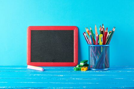blank black chalk frame, white chalk and school supplies on a blue background, concept back to school 版權商用圖片