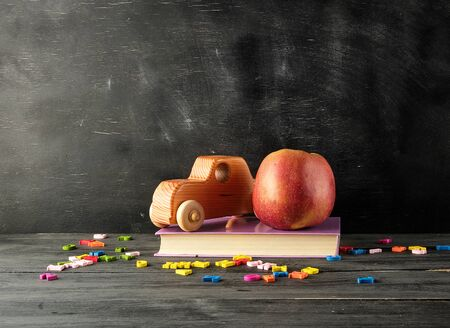 ripe red apple, ancient toy car stand on a book, background from an empty black chalk board