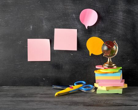 stack of multi-colored sticky stickers, glass globe, scissors on a black wooden background, concept back to school Stok Fotoğraf