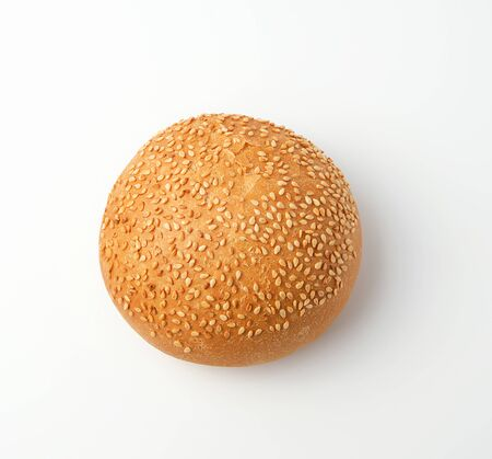 baked whole round bun with sesame seeds made from white wheat flour on a white background, top view