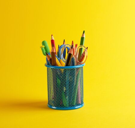 blue stationery glass with multi-colored wooden pencils and pens, yellow background, copy space