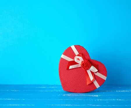 closed gift box in the form of a heart on a blue background, copy space