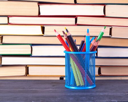 stacks of various hardback books and blue stationery glass with multi-colored wooden pencils, back to school concept Zdjęcie Seryjne