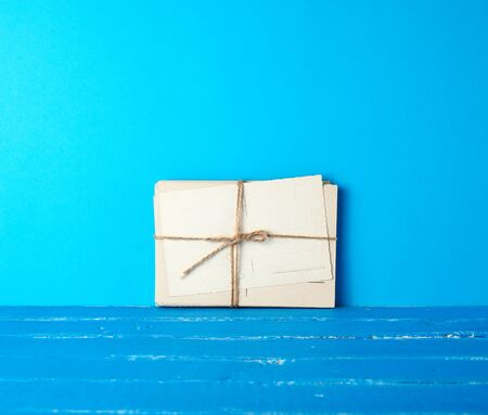 white paper cards tied with a rope on a blue wooden background, copy space