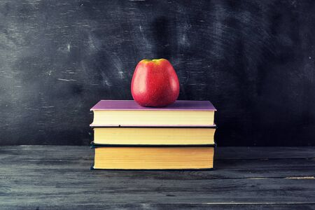 red ripe apple lies on a stack of books, black background, back to school
