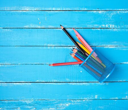 blue stationery glass with multi-colored wooden pencils, blue background, copy space