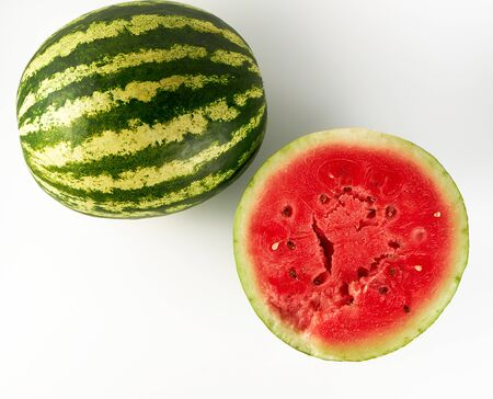 half ripe watermelon with red juicy pulp and seeds and a whole green on a white background, sweet summer berry, top view Stock Photo