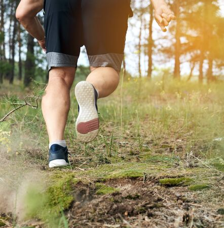 adult man in black shorts runs in the coniferous forest against the bright sun, concept of a healthy lifestyle and running in the fresh air, back view