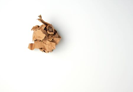 crumpled sheet of brown paper on a white background, close up, copy space Stock Photo