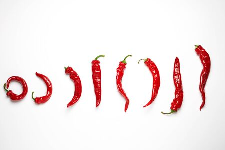 whole ripe red hot chili peppers on a white background, concept of distinction and discrimination