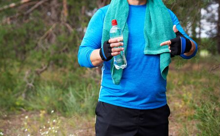 adult athlete is standing in the middle of nature in a blue uniform with a green towel, in one hand a transparent plastic water bottle with the other hand shows a gesture
