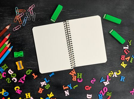 open spiral notebook with clean white sheets, wooden colored pencils on a black background, back to school backdrop