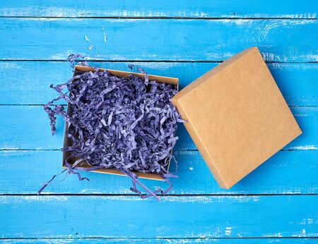 open empty brown craft box on a blue wooden background, top view, holiday backdrop