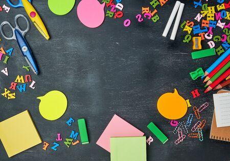 school supplies: multicolored wooden pencils, notebook, paper stickers, paper clips, pencil sharpener and white chalk, copy space
