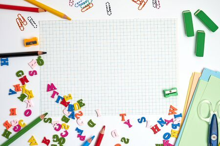 school supplies: multicolored wooden pencils,  notebook, colored paper and  blank white sheet in a check-box, back to school backdrop, copy space