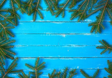 green branches of needles around the perimeter of a blue background from shabby boards, festive Christmas background, copy space Zdjęcie Seryjne