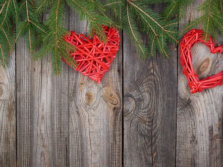 green branches of needles and red heart on a gray wooden background from old boards, festive Christmas background, copy space Zdjęcie Seryjne