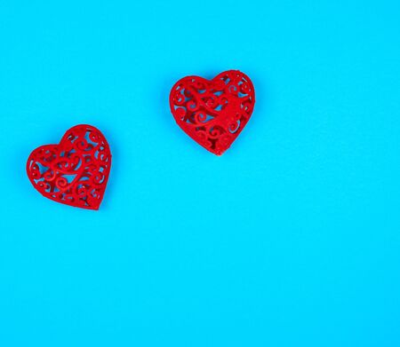 two red decorative hearts on a blue  background, copy space