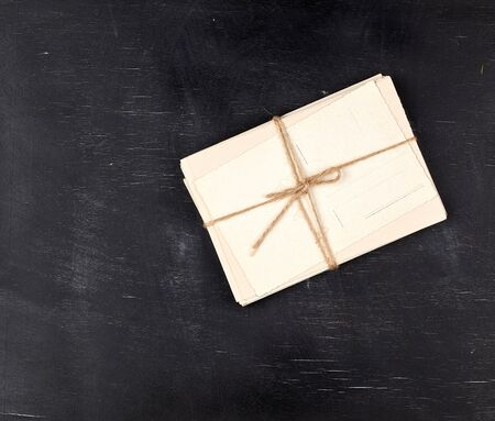 old empty white paper cards tied with a rope on a black wooden background, copy space