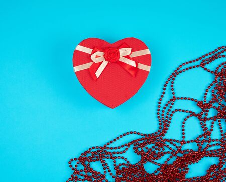 closed red gift box in the form of a heart with a bow on a blue background, copy space 写真素材