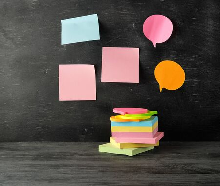 stack of multi-colored sticky stickers on a black wooden background, concept back to school Stok Fotoğraf