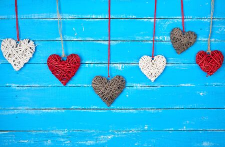 various wicker decorative hearts hanging on a rope, blue wooden background, festive backdrop