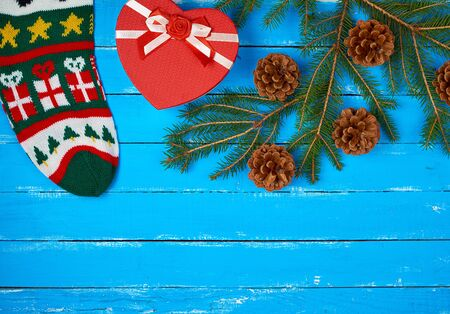 green spruce branch with brown cones, red box with bow and christmas sock, holiday backdrop