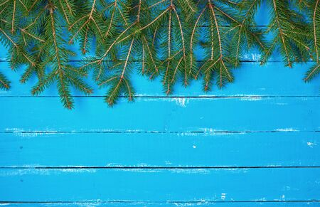 green branches of needles on a blue background from shabby boards, festive Christmas background, copy space