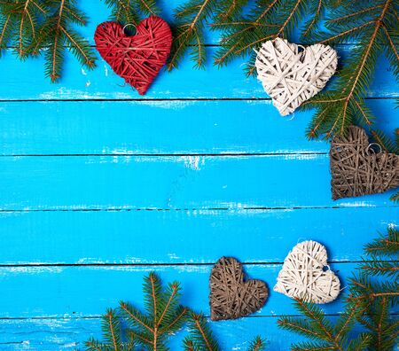 green branches of needles and decorative wicker hearts on a blue wooden background from boards, festive backdrop, copy space