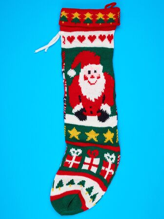knitted brightly colored Christmas sock for gifts on a blue background, holiday backdrop