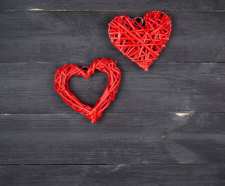 two wicker red hearts on a black background, holiday background, copy space