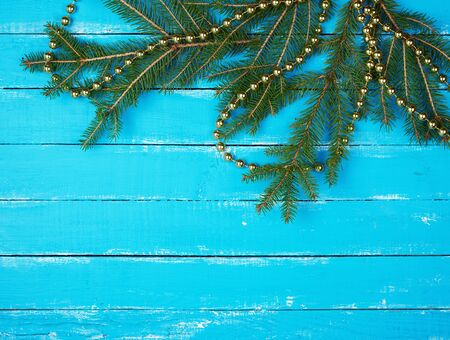 green branches of needles and yellow Christmas garland on a blue wooden background from boards, copy space Zdjęcie Seryjne