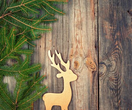 green branches of spruce, wooden toy deer on an old gray wooden background, holiday backdrop, copy space