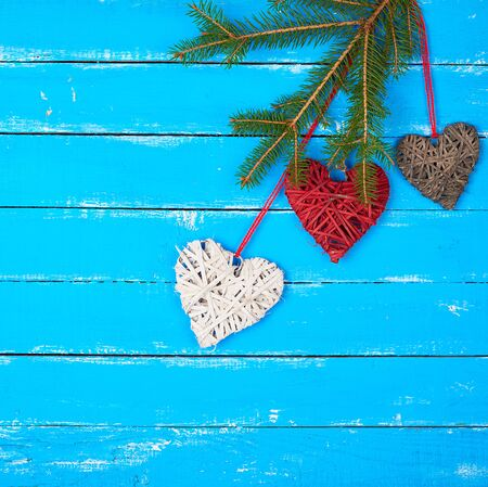 various wicker decorative hearts and green spruce branch, blue wooden background, festive backdrop