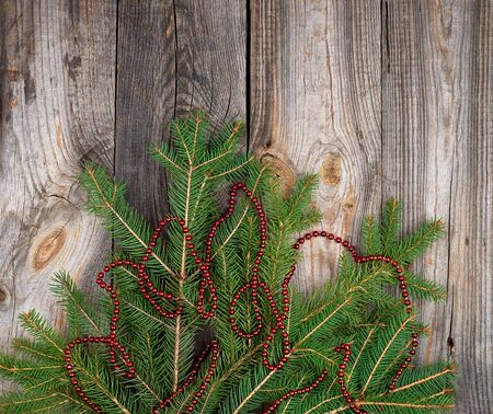 green branches of needles and red Christmas garland on a gray wooden background from boards, copy space Zdjęcie Seryjne