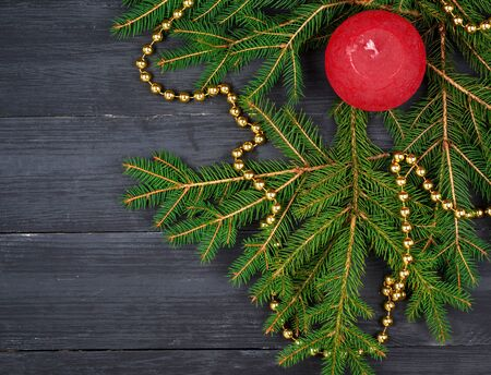 green spruce branches and Christmas red candle on a black wooden background, top view