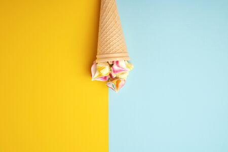 Multi-colored baked meringues in a waffle cup on a blue-yellow background, flat lay