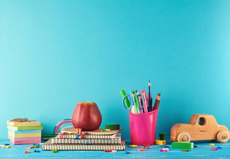 School supplies: notebook, pencils, stickers, scissors on a blue background, concept of back to school 版權商用圖片