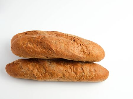 Stack of whole baked baguettes from rye flour on a white background, top view