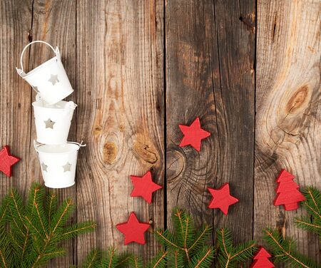 Green spruce branches and Christmas decor on a gray wooden background, top view