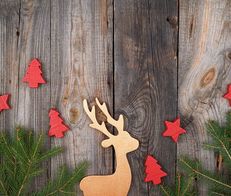 Green branches of spruce, wooden toy deer on an old gray wooden background, holiday backdrop, copy space Reklamní fotografie