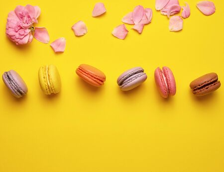 sweet multi-colored macaroons with cream and a pink rose bud with scattered petals on a yellow  background, top view, flat lay, copy space