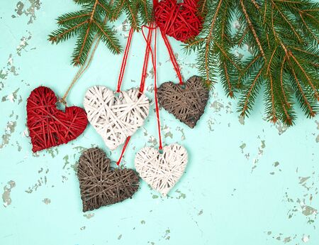 green branches of spruce and wicker hearts on a rope, green background, top view