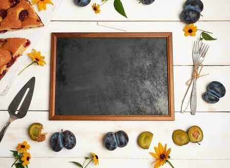 empty chalky black frame ingredients and slices of plum cake on a white wooden table, top view Imagens