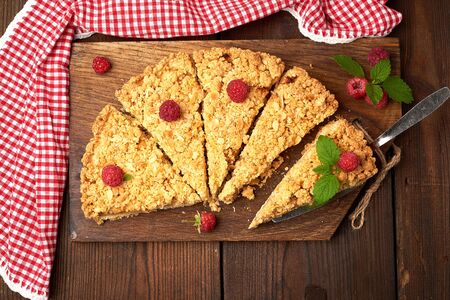 sliced triangular pieces of crumble pie with apples on a brown wooden board, top view Banco de Imagens