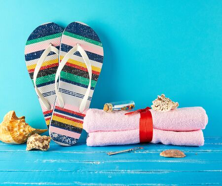 pair of female beach slippers and a pink towel on a blue background, copy space,  concept of a vacation at sea