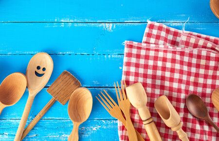 many different wooden spoons, forks  on a blue background, copy space, kitchen backdrop