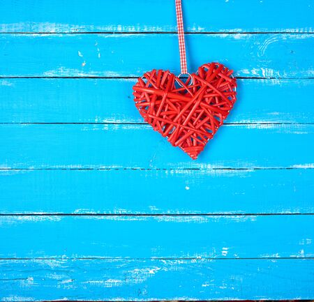 wicker red heart on a blue wooden background, copy space